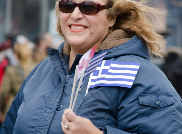 a woman with dark sunglasses and blue coat holds three small flags, two Greek and one Canadian
