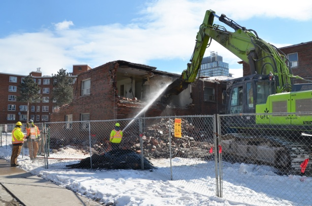 workmen spray water as a machine arm pulls apart a building that is in the process of being demolished