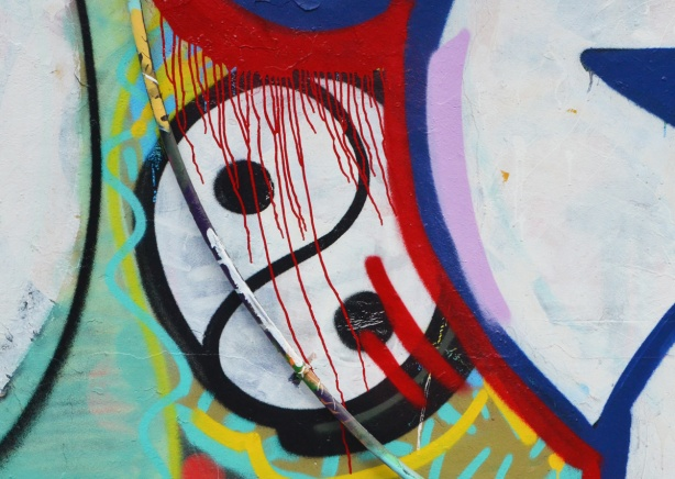 close up of a spray paint artwork in alley, a yin yang symbol in black and white with red drips of paint running through it