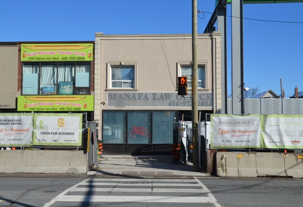 crosswalk leading to buildings, stores beside the construction of Oakwood LRT station, concrete barriers and fence in front of most of them, Manafa Law office and Asian massage therapy centre, signs saying open for business, Eglinton Avenue West, crosstown construction