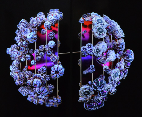 ornate circular shapes like beads and flowers in shades of blue and purple on a black background, a video playing on a wall