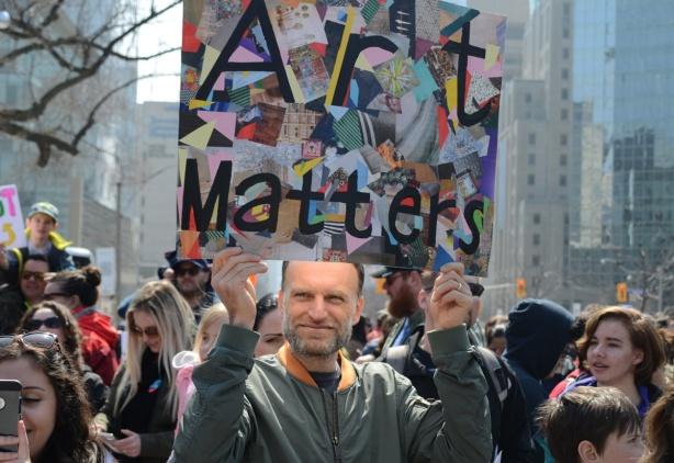 person holding a placard protesting Doug Fords proposed cuts to education funding, says art matters. Crowds at a protest at Queens Park,
