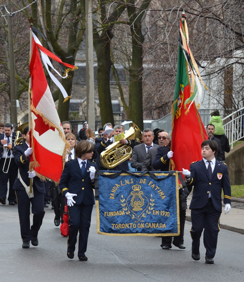 banner and flag carriers for Banda L N S de fatima, a Portuguese band from toronto, as they march in a parade