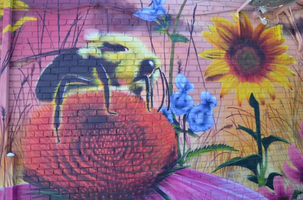 part of a nick sweetman pollinators mural, a bee on top of a purple coneflower