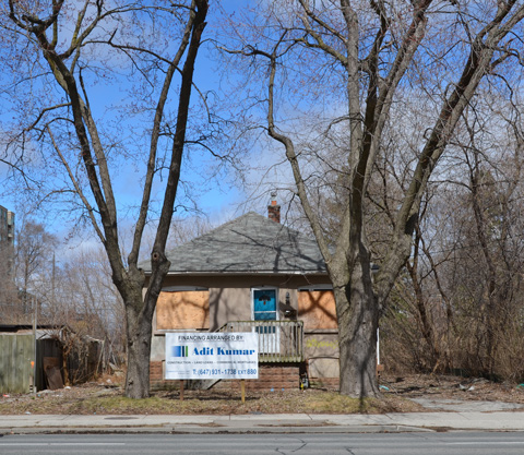 small bungalow with blue door, windows boarded up, large tree in front yard, sign in front yard advertising financing