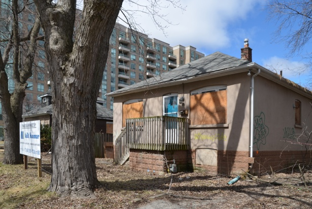 small bungalow with blue door, windows boarded up, large tree in front yard, apartment building behind,