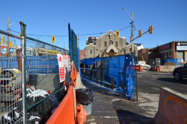 blue fences between sidewalk and rad at Eglinton and Dufferin, construction, church in the background,