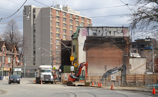 construction on dundas street, a vacant lot where a building was demolished, construction equipment and a dump truck working at the site, old building beside