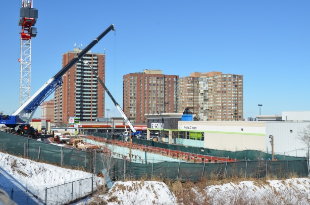 three apartment buildings in the background, construction in foreground, in front of a grocery store, snow on the ground, green fence around the construction