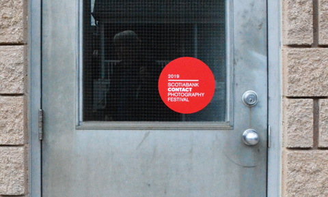 red circular sticker on a window, marking a gallery that is participating in contact photography festival