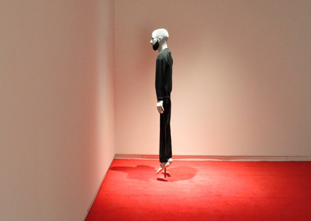 a mannequin top, of a bald man, on a frame with black loose fitting clothes, stands on a red carpets facing the corner, nothing else is in the room