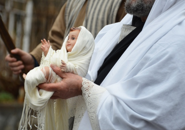 a bearded priest carrying a baby doll wrapped in white swaddling clothes in a passion procession
