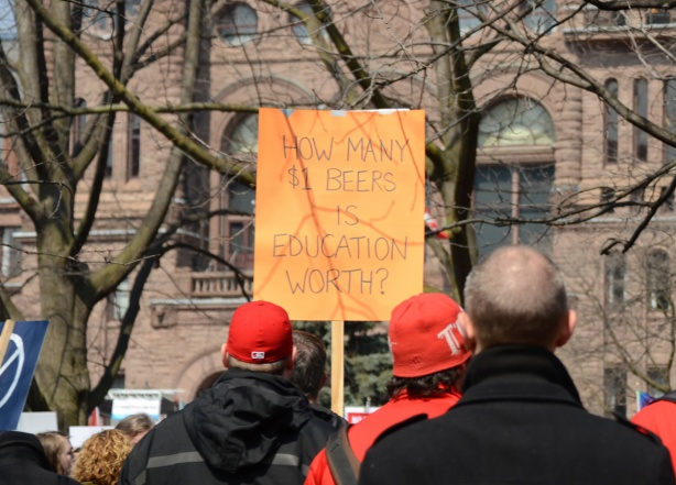 person holding a placard protesting Doug Fords proposed cuts to education funding, back to camera, with a group of men, sign says how many dollar beers is education worth
