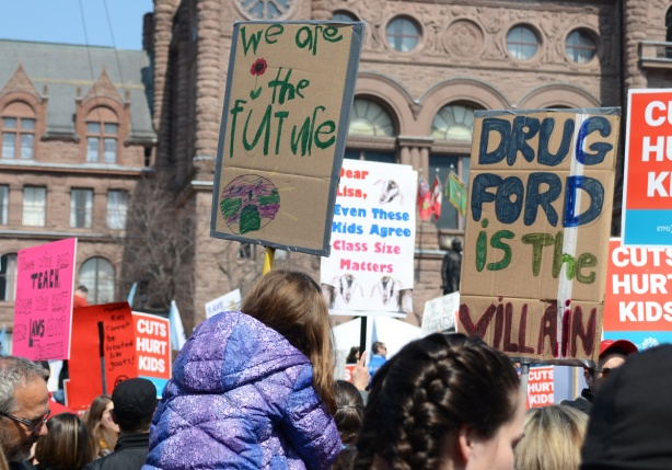 two hand made signs on brown cardboard, one says we are the future and the other says Doug Ford in the villain.  Both drawn and made by kids and being held by kids.   Queens Park education budget protest