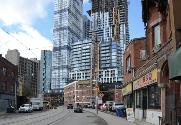 dundas street east, looking back towards downtown from Sherbourne street, new condos and highrises in steel and glass overwhelming the older shorter buildings on Dundas such as Filmores Hotel and Georges pizza