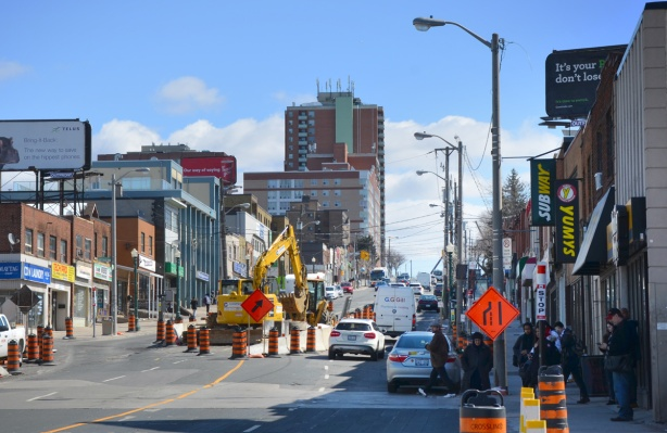 street scene, traffic and stores, construction in the middle of the street, Eglinton Avenue looking wast from Keele street