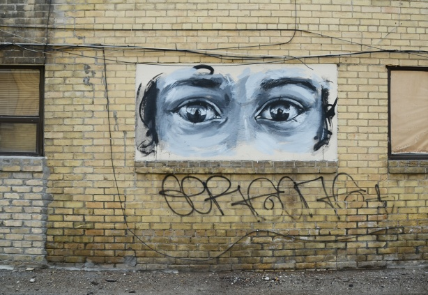 a black and white painting on a wall of a very large pair of eyes, very realistic looking, black and white, on a yellowish brick wall