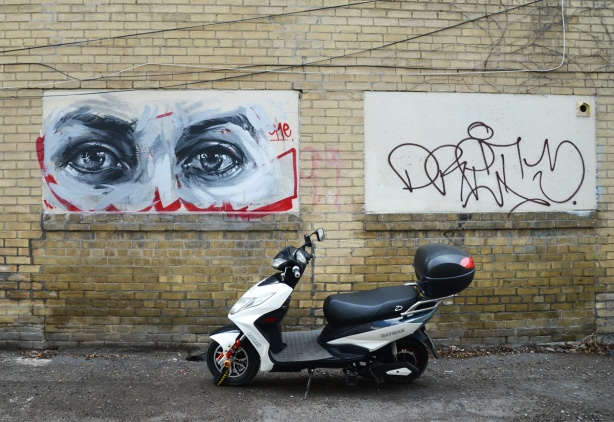 black and white realistic painting of a pair of eyes, larger than life, on a yellowish brick wall.  A small motorcycle is parked in front of the wall.
