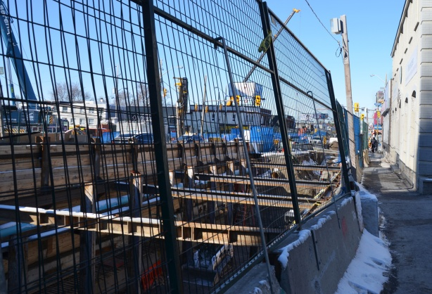 wire mesh fence in front of open pit excavation of underground LRT, steel cross beams and wood supports,
