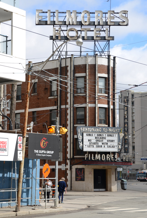 Filmores Hotel with large sign above the hotel and a black and white sign over the front entrance, old brick building