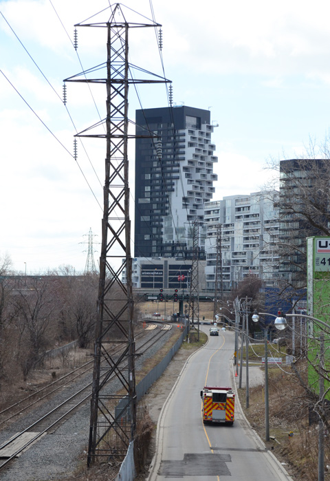 looking south on Bayview street from Dundas as it passes large metal hydro poles, also new development (condos) in East Don Lands, fire truck on road