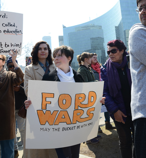 person holding a placard protesting Doug Fords proposed cuts to education funding, signs says Ford Wars