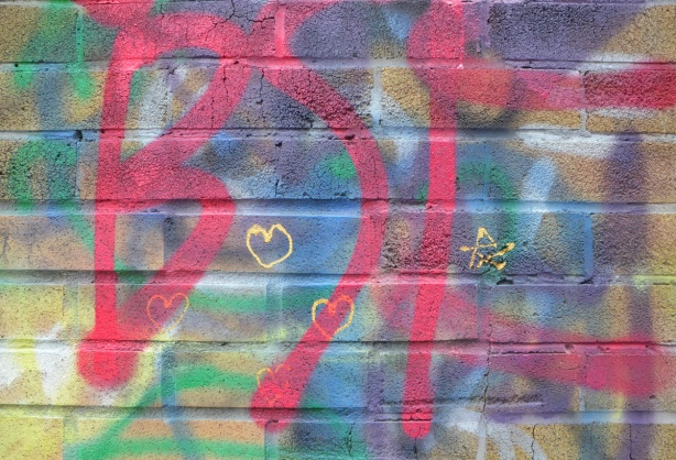 three tiny yellow hearts and a tiny yellow star drawn on a wall with colourful spray paint graffiti