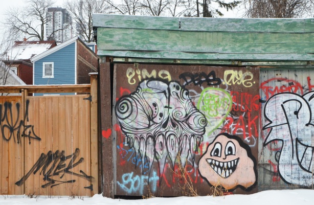 a grominator piece of graffiti and a pink smiley face monster, both on a brown garage door in an alley