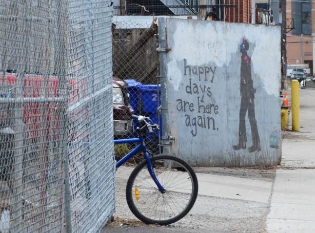 a blue bike leans against a chainlink fence, behind it is a piece of street art that says happy days are here again, with painting of a man walking