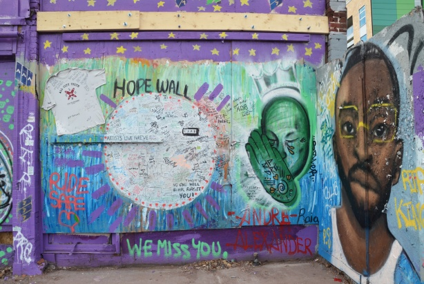 wall, plywood hoardings, covered with paint and graffiti as a Hope Wall, in memory of Andre Alexander who was killed when hit by a car. painting of his face, plus large space for people to write messages, on Spadina near Kensington Market,