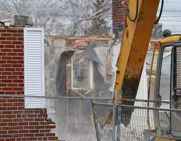 close up of a digger demolishing a house