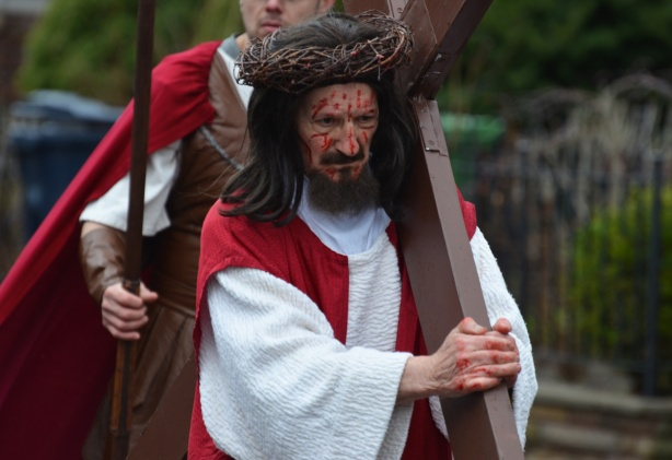 a man with a crown of thorns and blood on his face and carrying a large cross walks in a parade, with a man behind him dressed as a roman soldier