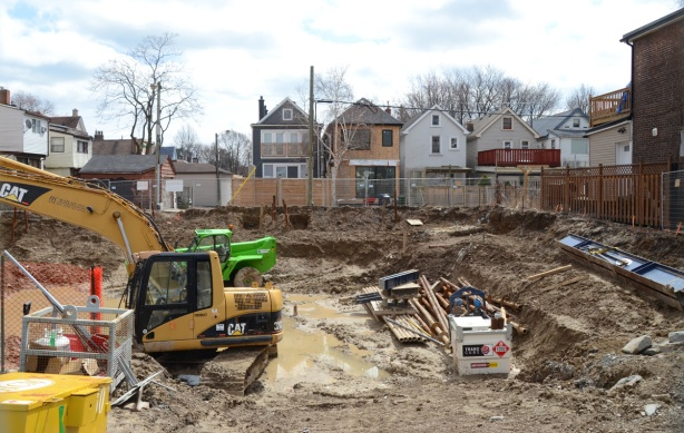 a construction site, a hole in the ground, with backs of houses behind the find surrounding it