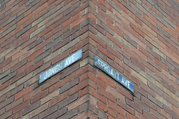 two old Toronto street signs, blue metal, attached to a house at Jones Ave and Sproat Ave