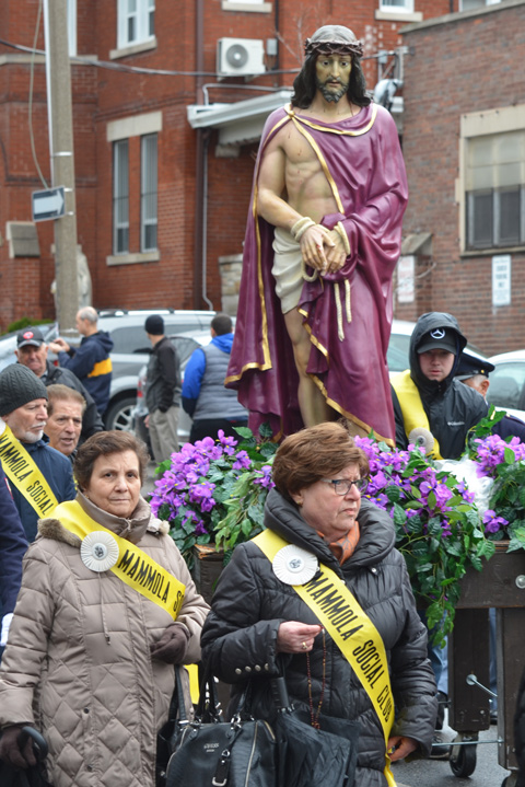 people from the Mammola Social Club, wearing yellow sashes, push a cart on wheels with a statue of Jesus in a passion of Christ procession on the streets