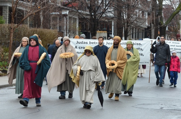 small group of men in a parade, wearing long robes and carrying bread in the shape of a large wreath, a banner is behind them that describes the betrayal of Jesus by Judas