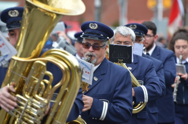 men in blue uniforms and blue hands marching in a band, tuba player in the foreground,
