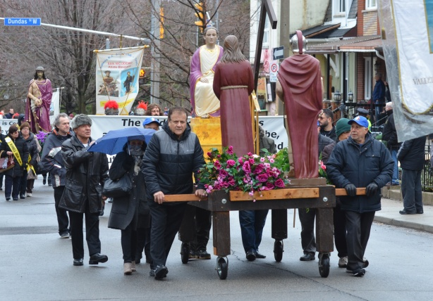 a group of people push a large flat wooden cart on wheels on a parade, cart has statues of it, characters from the story of the passion of christ, the events leading up to the crucifixion