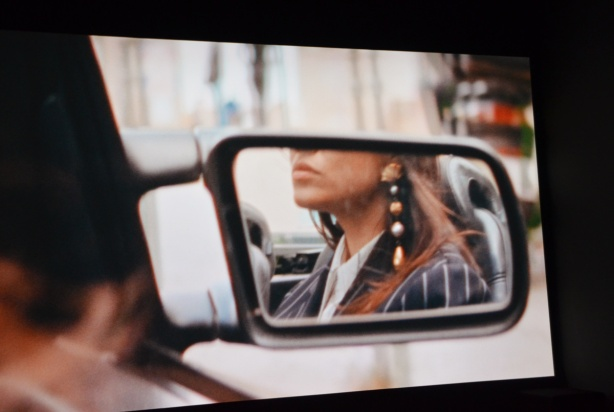 picture from a video, a woman's reflection in the side mirror of a car, long hair, long dangly ear rings