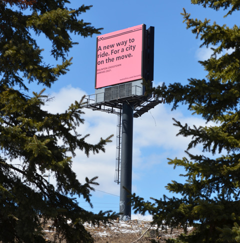 pink billboard seen between pine trees, raised high, words on it that say A new way to ride. For a city on the move. Eglinton Crosstown arrives 2021.