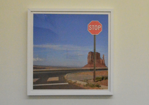 a large frames photo on a wall of rock formation in Monument Valley USA with a stop sign in the foreground