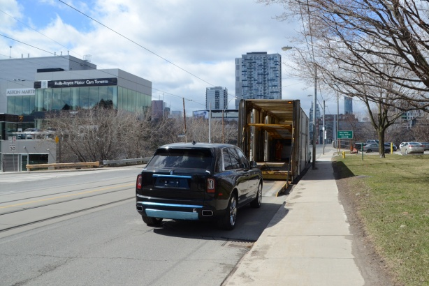 a brand new black Bentley car being unloaded from a truck