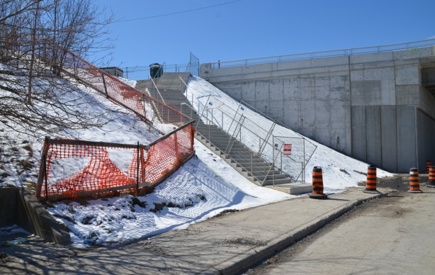 new concrete steps, still fenced off, up a hill with a light covering of snow to a new bridge