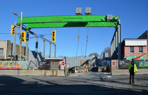 large green overhead crane on steel runners, hanging over a construction site