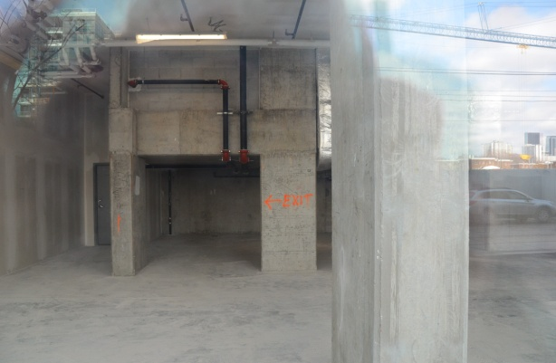 looking through the window of a building under construction, concrete walls, some black pipes, also in orange paint the word exit with an arrow
