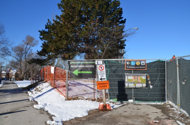 a sidewalk ends at a fence arond a construction site and pedestrians are diverted through a park to the left, signs on the fence directing traffic
