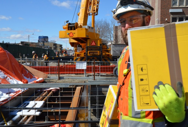 a workman in a hard hat and carrying yellow packages walks in front of the camera on a construction site