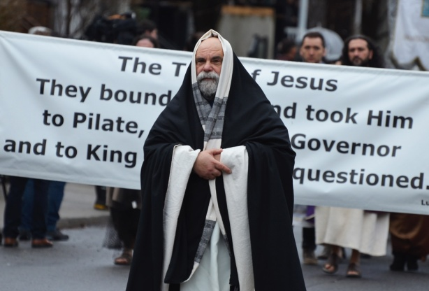 a man dressed as a priest in long black and white robes walks in a passion of christ procession in front of a large banner that has a bible verse from Luke 23
