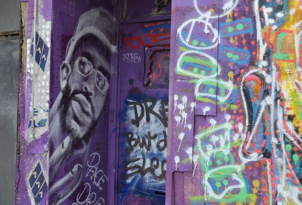 wall and doorway painted purple, a black man's face in greys on one side of the entranceway, other graffiti too