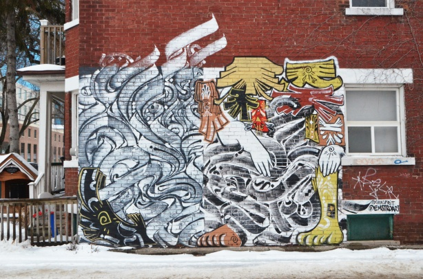 large mural on the side of a red brick house